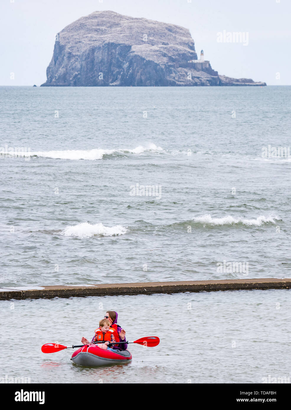 North Berwick, East Lothian, Scotland, United Kingdom, 14th June 2019. UK Weather: After East Lothian suffered heavy rain the last few days, the weather has brightened, and people enjoy the outdoor pursuits in the seaside town. A woman and child  ina rubber dinghy in the tidal bathing pool at Milsey Bay with the Bass Rock colony on the horizon. Credit: Sally Anderson/Alamy Live News - Stock Image
