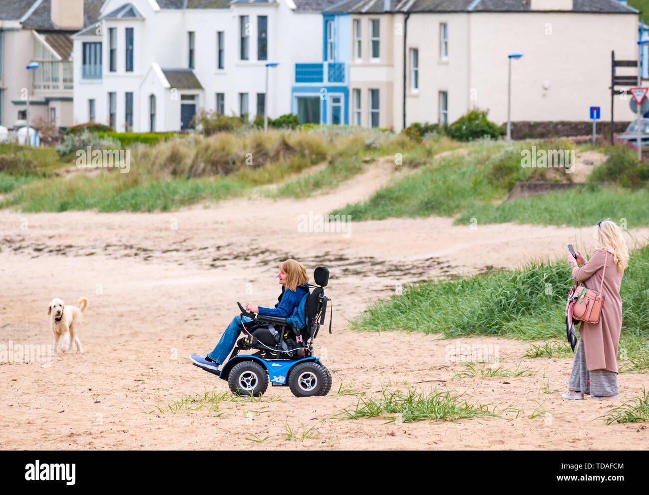 North Berwick, East Lothian, Scotland, United Kingdom, 14th June 2019. UK Weather: After East Lothian suffered heavy rain the last few days, the weather has brightened, and people enjoy the outdoor pursuits in the seaside town. A woman enjoys trying out an electric wheelchair on the beach at Milsey Bay. Credit: Sally Anderson/Alamy Live News - Stock Image