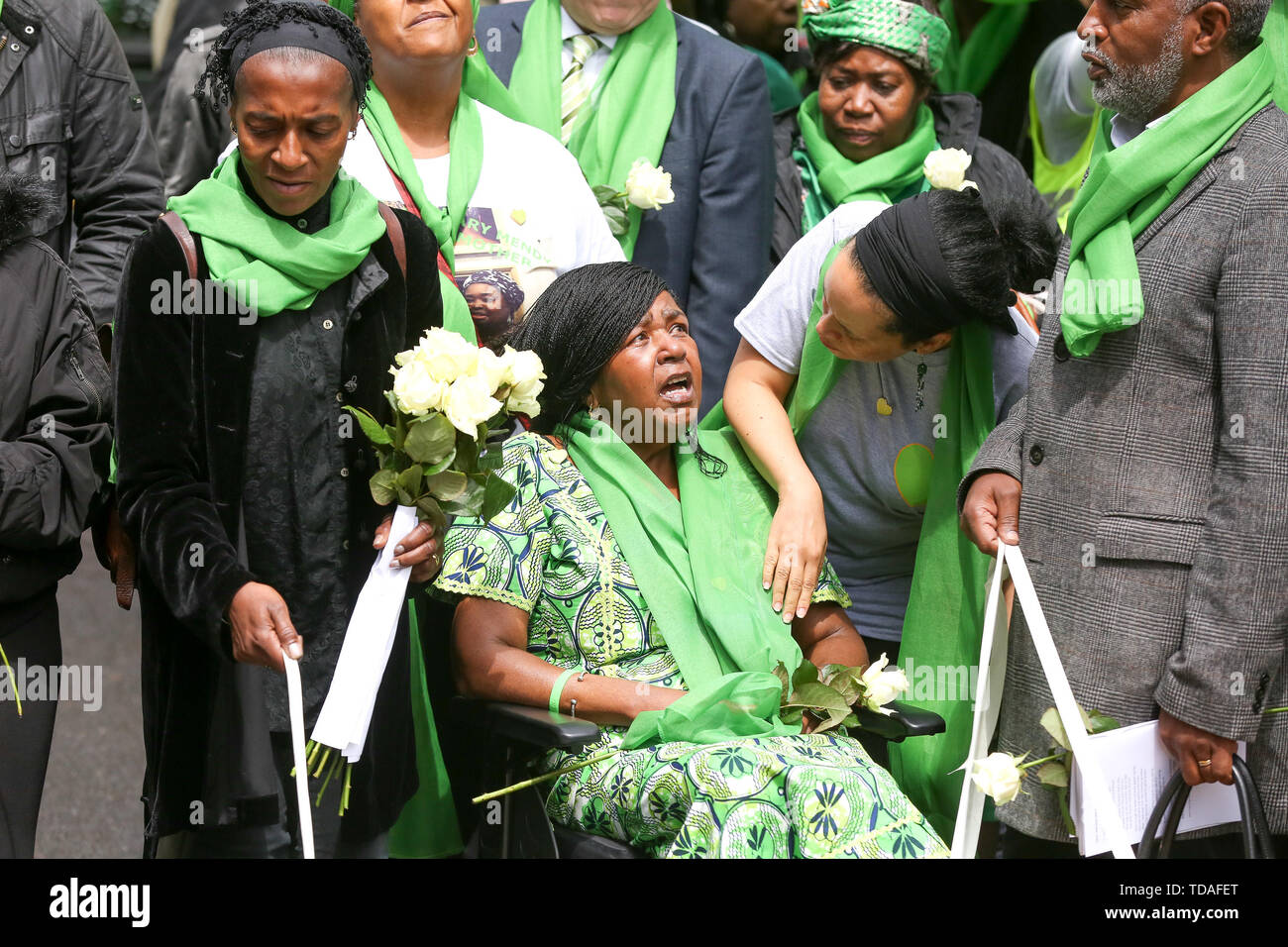 North Kensington, West London. UK 14 Jun 2019 - An emotional woman wear symbolic green scarf outside St HelenÕs Church take part to commemorate the second anniversary of the Grenfell Tower fire. On 14 June 2017, just before 1:00Êam a fire broke out in the kitchen of the fourth floor flat at the 24-storey residential tower block in North Kensington, West London, which took the lives of 72 people. More than 70 others were injured and 223 people escaped.   Credit: Dinendra Haria/Alamy Live News - Stock Image