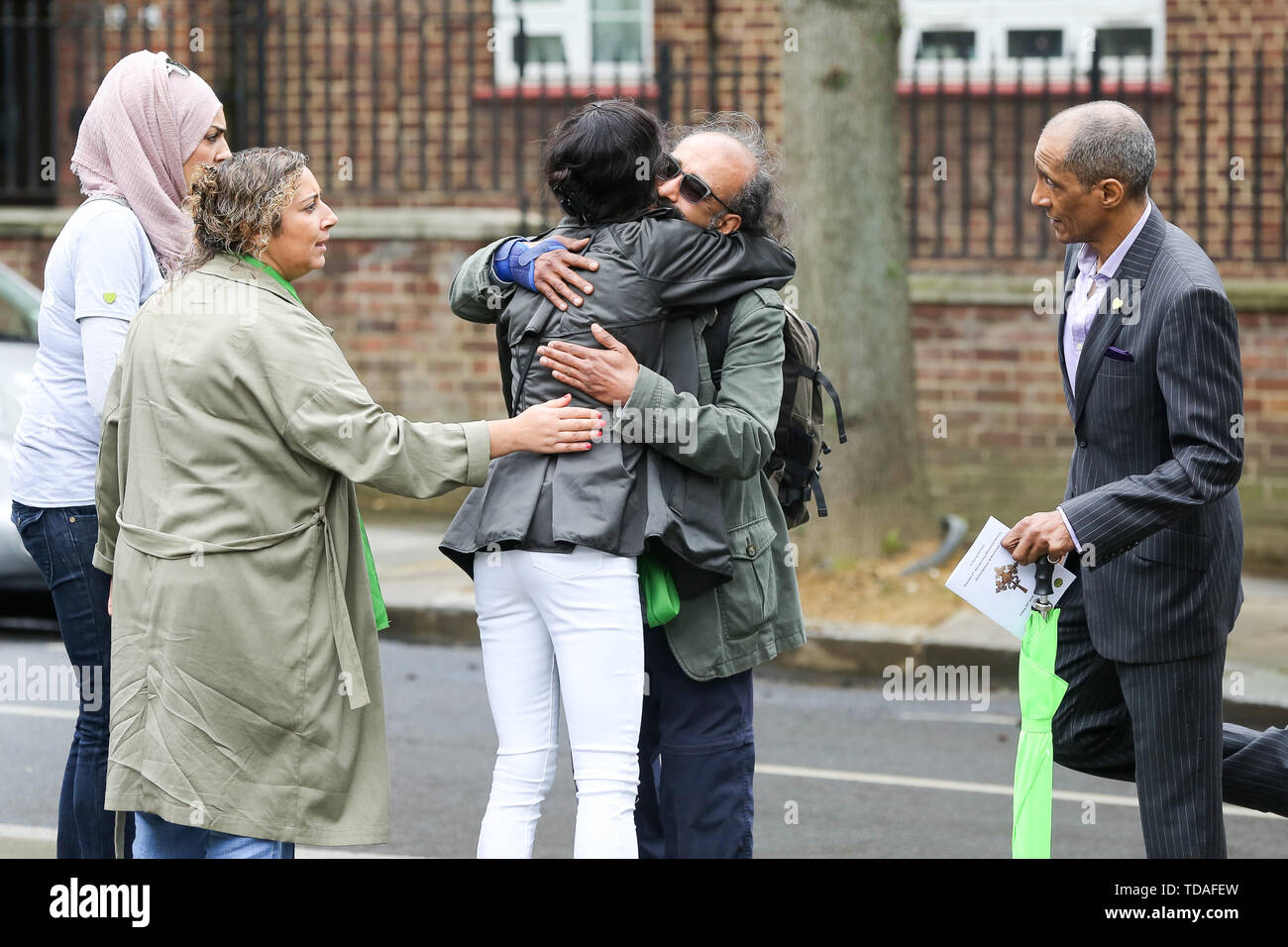 North Kensington, West London. UK 14 Jun 2019 - Survivors, family and friends of the victims arrive at St Helen's Church with floral tributes to commemorate the second anniversary of the Grenfell Tower fire. On 14 June 2017, just before 1:00Êam a fire broke out in the kitchen of the fourth floor flat at the 24-storey residential tower block in North Kensington, West London, which took the lives of 72 people. More than 70 others were injured and 223 people escaped.  Credit: Dinendra Haria/Alamy Live News - Stock Image
