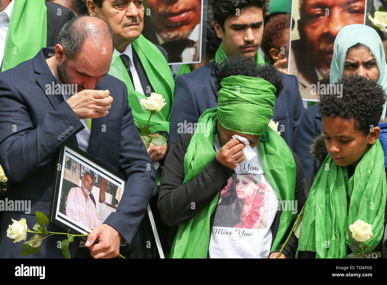 North Kensington, West London. UK 14 Jun 2019 - Survivors, family and friends wearing symbolic green scarf outside St Helen's Church following a service at  to commemorate the second anniversary of the Grenfell Tower fire. On 14 June 2017, just before 1:00Êam a fire broke out in the kitchen of the fourth floor flat at the 24-storey residential tower block in North Kensington, West London, which took the lives of 72 people. More than 70 others were injured and 223 people escaped.  Credit: Dinendra Haria/Alamy Live News - Stock Image