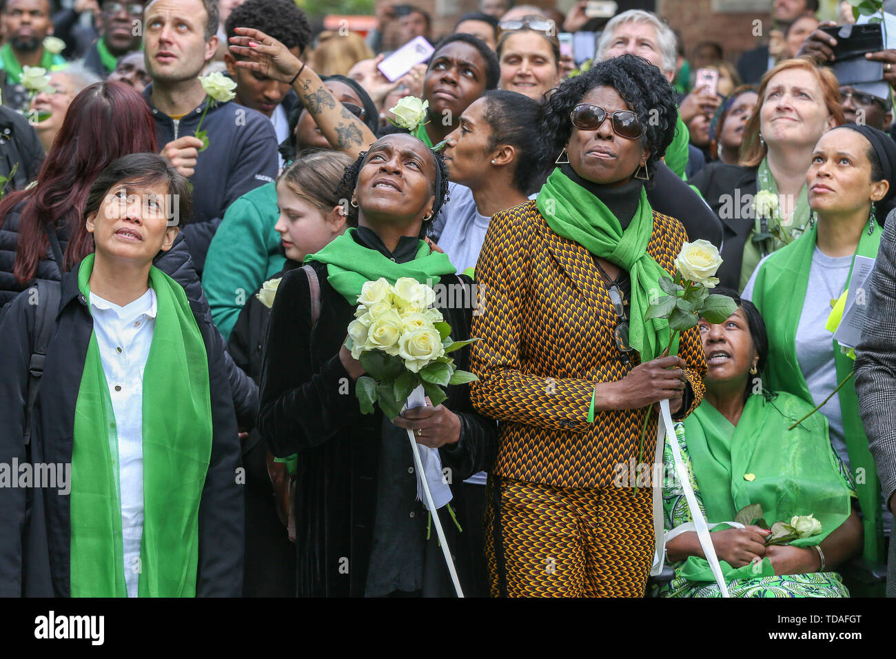 North Kensington, West London. UK 14 Jun 2019 -  Survivors, family and friends of the victims wear symbolic green scarf look at the white doves after been released to commemorate the second anniversary of the Grenfell Tower fire. On 14 June 2017, just before 1:00Êam a fire broke out in the kitchen of the fourth floor flat at the 24-storey residential tower block in North Kensington, West London, which took the lives of 72 people. More than 70 others were injured and 223 people escaped.  Credit: Dinendra Haria/Alamy Live News - Stock Image