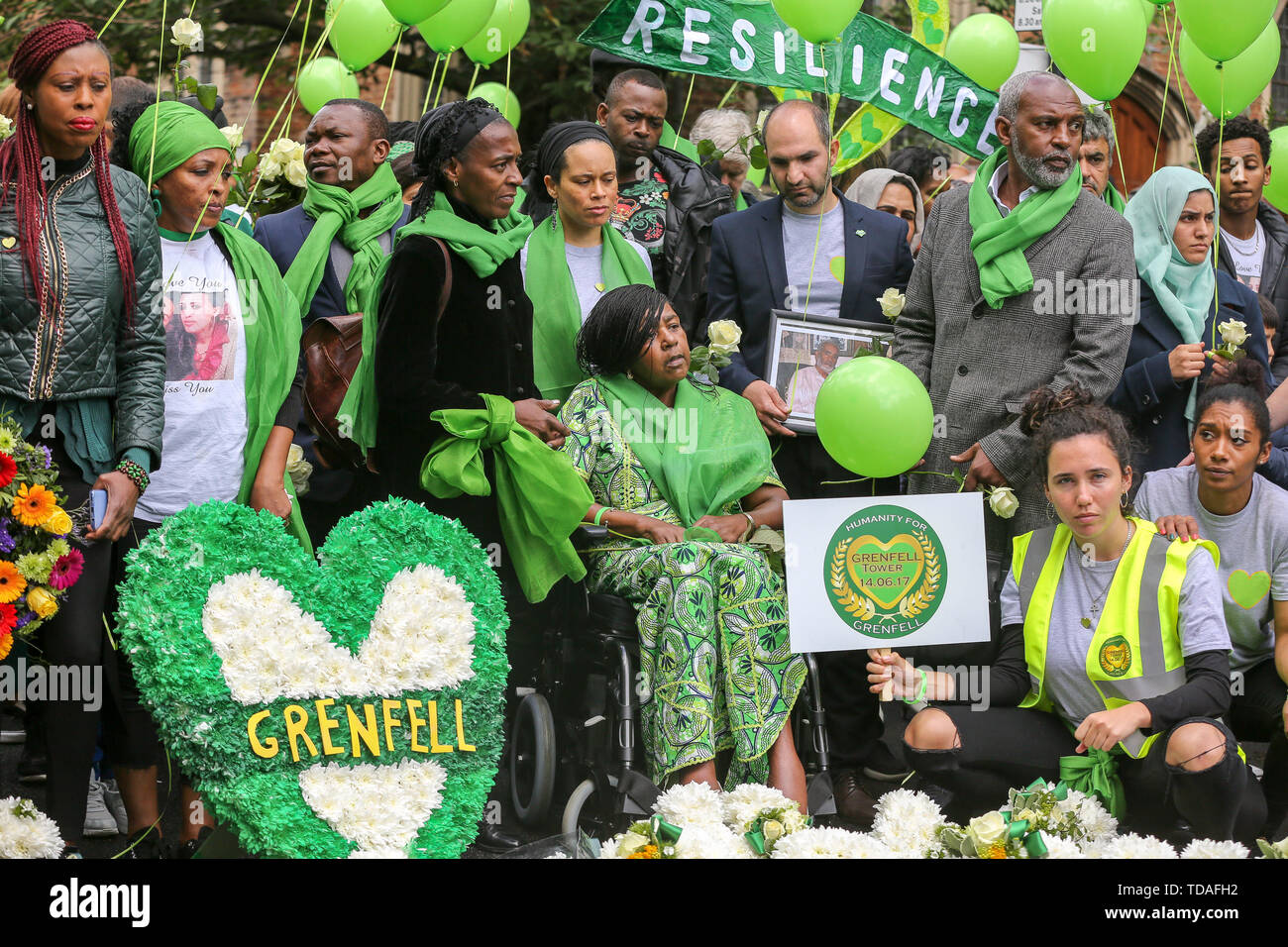 North Kensington, West London. UK 14 Jun 2019 - Survivors, family and friends of the victims wear symbolic green scarf to commemorate the second anniversary of the Grenfell Tower fire. On 14 June 2017, just before 1:00Êam a fire broke out in the kitchen of the fourth floor flat at the 24-storey residential tower block in North Kensington, West London, which took the lives of 72 people. More than 70 others were injured and 223 people escaped.   Credit: Dinendra Haria/Alamy Live News - Stock Image