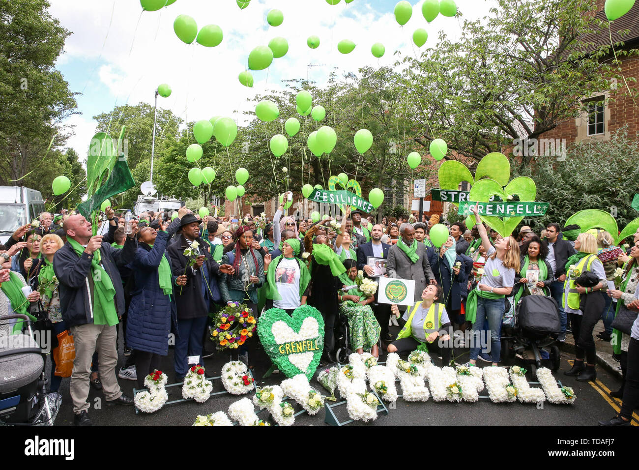 North Kensington, West London. UK 14 Jun 2019 - Survivors, family and friends of the victims wear symbolic green scarf release green balloons to commemorate the second anniversary of the Grenfell Tower fire. On 14 June 2017, just before 1:00Êam a fire broke out in the kitchen of the fourth floor flat at the 24-storey residential tower block in North Kensington, West London, which took the lives of 72 people. More than 70 others were injured and 223 people escaped.  Credit: Dinendra Haria/Alamy Live News - Stock Image