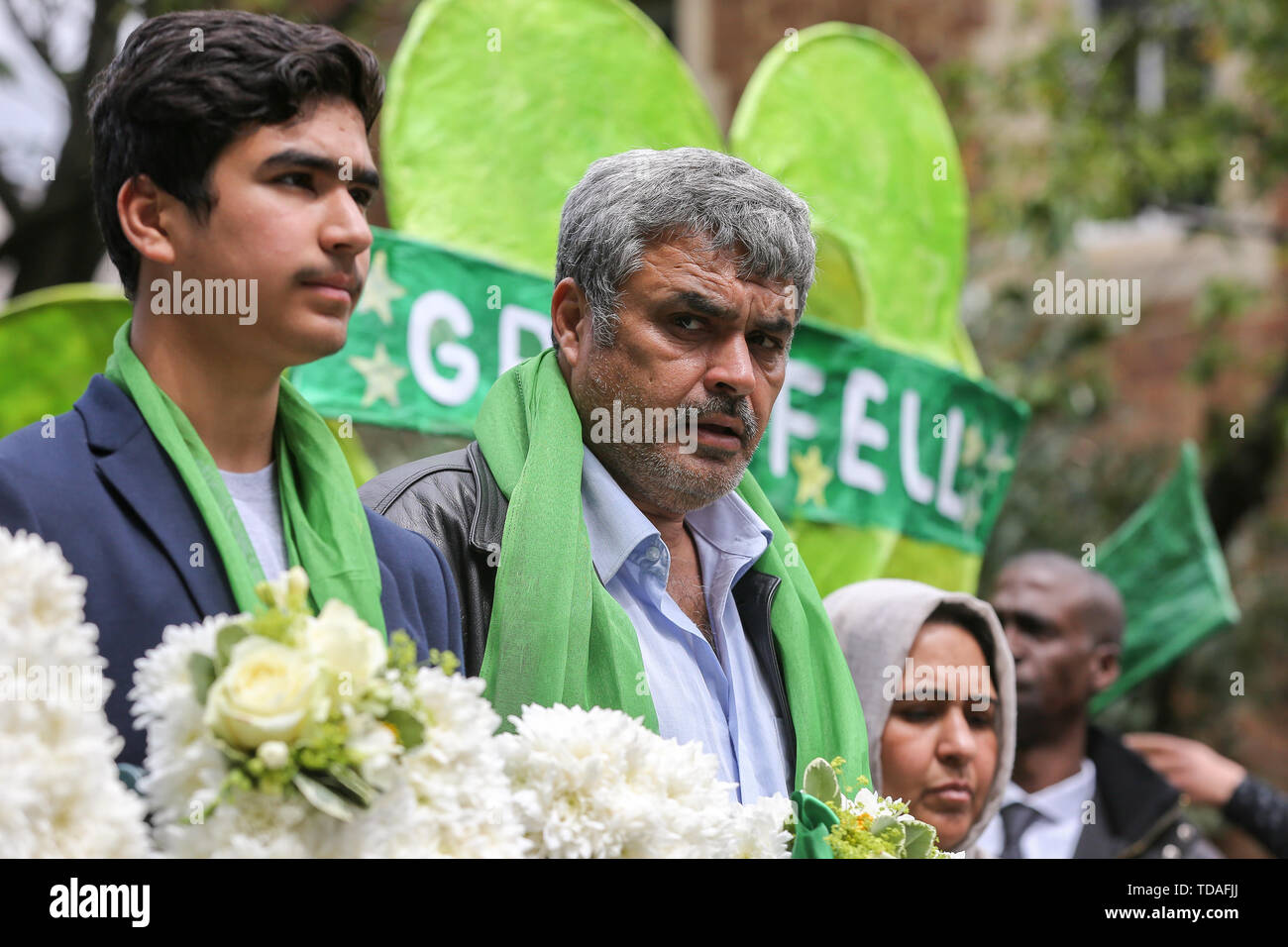 North Kensington, West London. UK 14 Jun 2019 - Survivors, family and friends of the victims wear symbolic green scarf take part in a silent procession marching from St HelenÕs Church to Grenfell Tower to commemorate the second anniversary of the Grenfell Tower fire. On 14 June 2017, just before 1:00Êam a fire broke out in the kitchen of the fourth floor flat at the 24-storey residential tower block in North Kensington, West London, which took the lives of 72 people. More than 70 others were injured and 223 people escaped.  Credit: Dinendra Haria/Alamy Live News - Stock Image