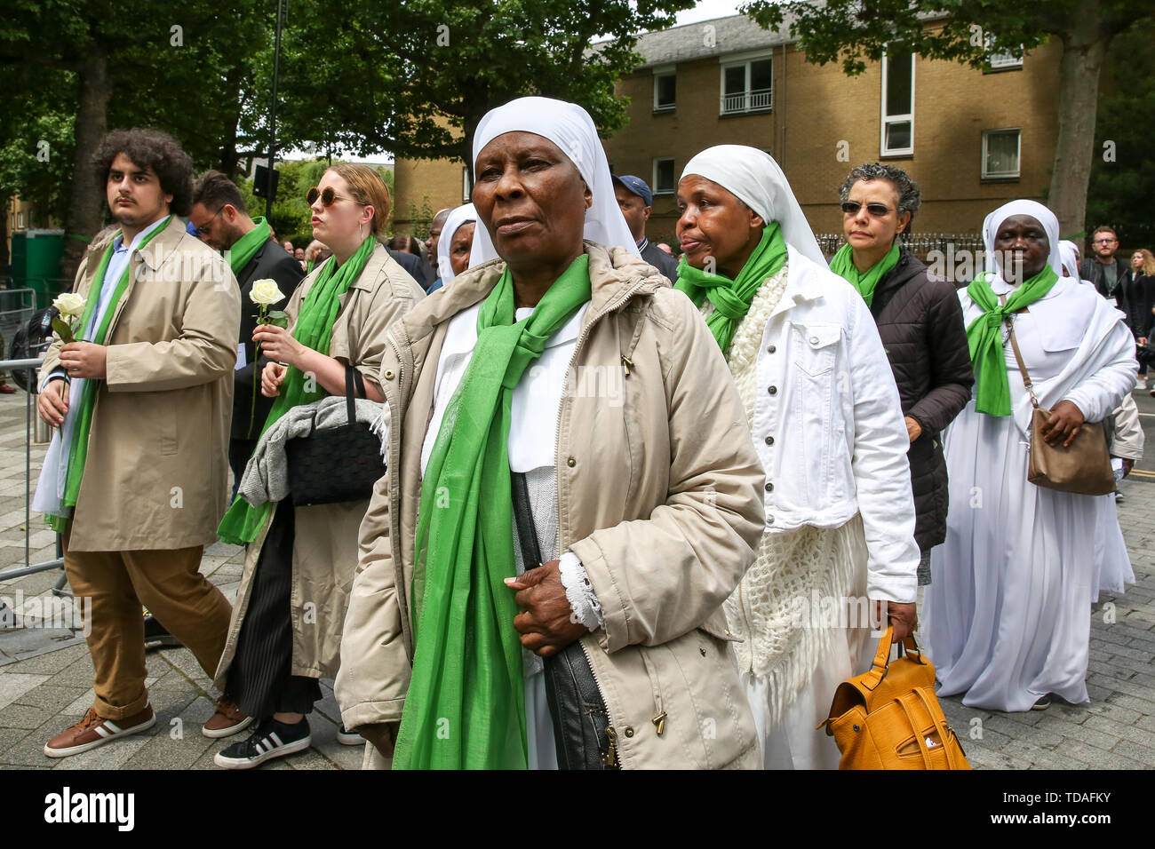 North Kensington, West London. UK 14 Jun 2019 - Nuns take part in a silent procession with the Grenfell Tower in the background to commemorate the second anniversary of the Grenfell Tower fire. On 14 June 2017, just before 1:00Êam a fire broke out in the kitchen of the fourth floor flat at the 24-storey residential tower block in North Kensington, West London, which took the lives of 72 people. More than 70 others were injured and 223 people escaped.  Credit: Dinendra Haria/Alamy Live News - Stock Image