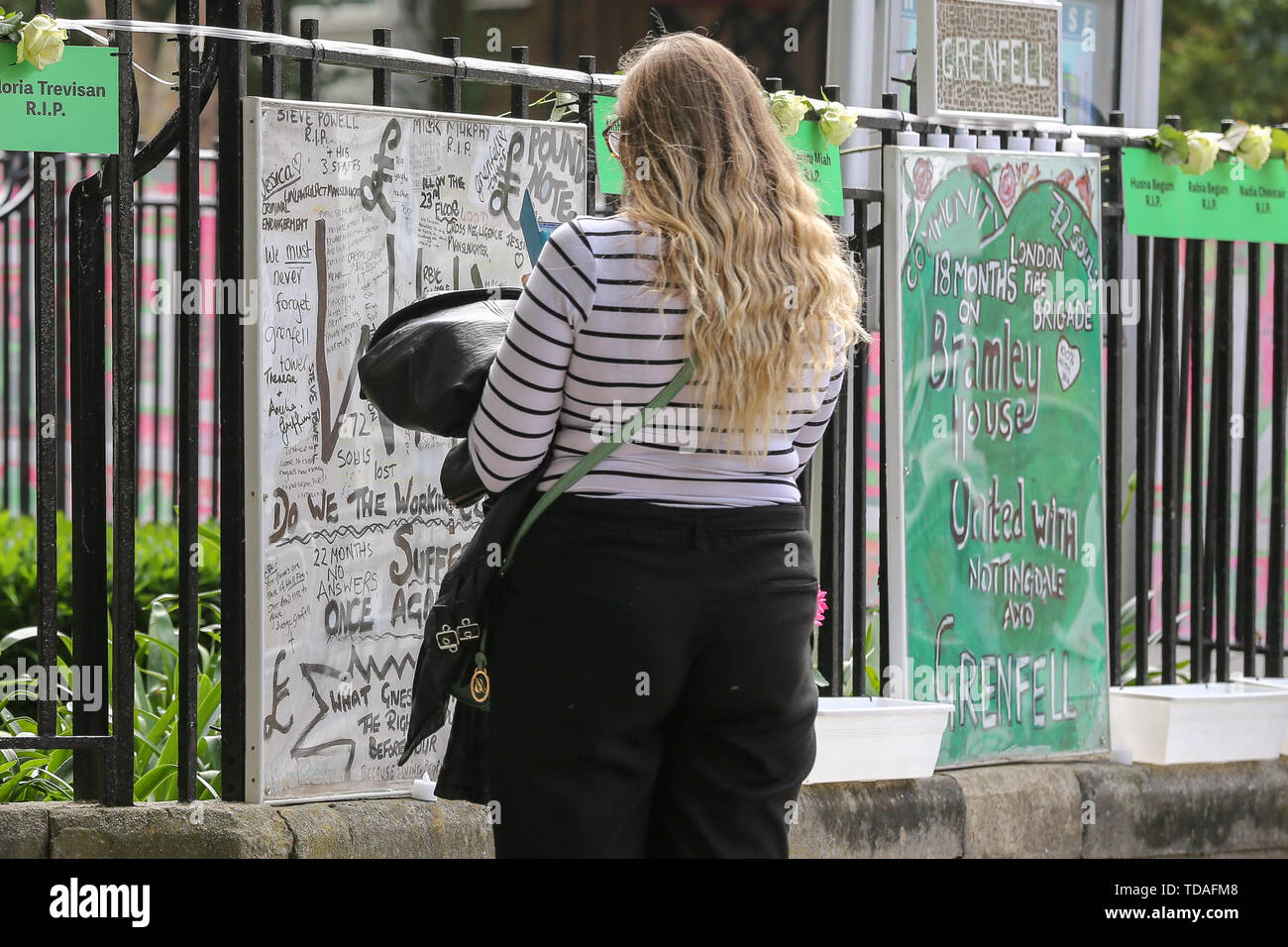 North Kensington, West London. UK 14 Jun 2019 - A woman reads the messages hung on the railing on a nearby block of flats. On 14 June 2017, just before 1:00Êam a fire broke out in the kitchen of the fourth floor flat at the 24-storey residential tower block in North Kensington, West London, which took the lives of 72 people. More than 70 others were injured and 223 people escaped.  Credit: Dinendra Haria/Alamy Live News - Stock Image
