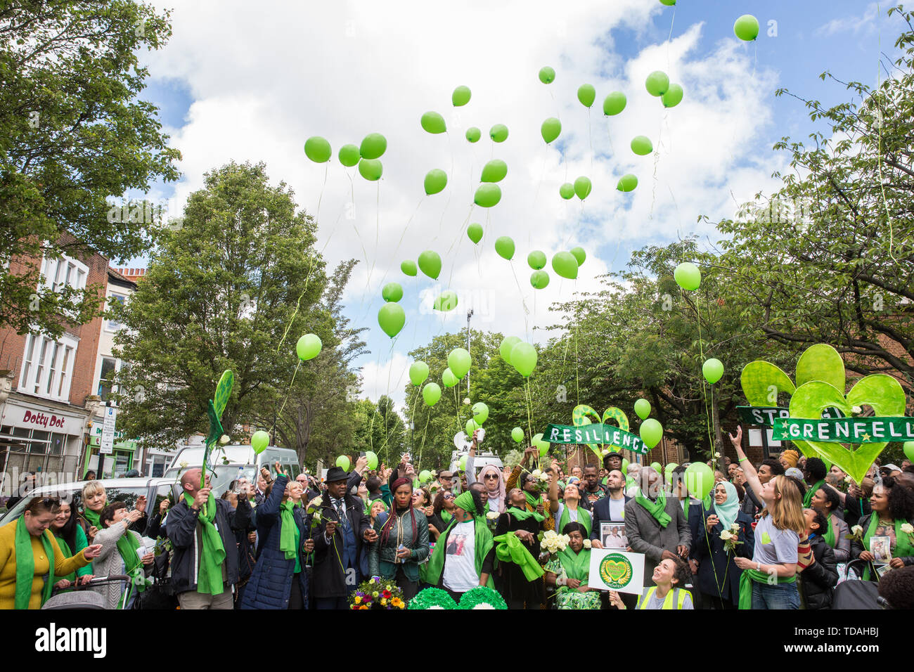 London, UK. 14 June, 2019. Family members release green balloons following a memorial service at St Helen's Church to mark the second anniversary of the Grenfell Tower fire on 14th June 2017 in which at least 72 people died and over 70 were injured. Credit: Mark Kerrison/Alamy Live News - Stock Image