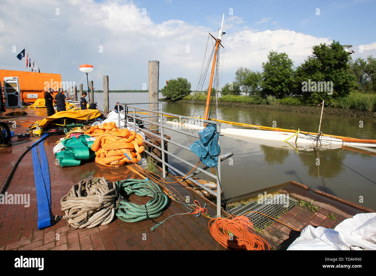 """Stadersand, Germany. 14th June, 2019. Employees of a Spanish company are preparing to salvage the sunken historic sailing ship """"No 5 Elbe"""" in the port of Stadersand. The historic sailing ship, which has only recently been extensively renovated, collided with a container ship on the Elbe and sank. Credit: Bodo Marks/dpa/Alamy Live News Stock Photo"""