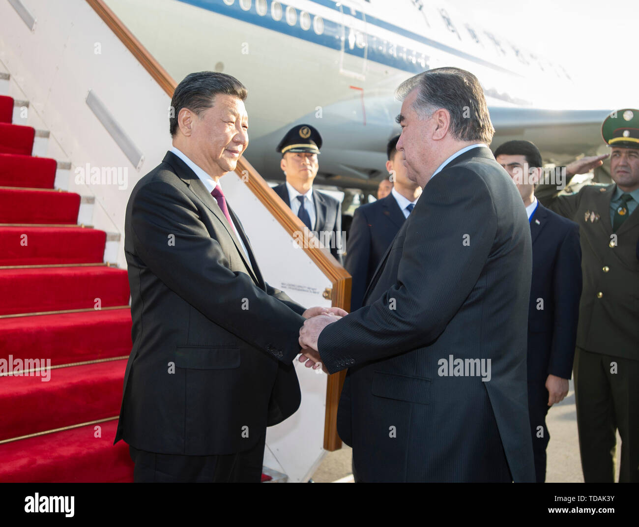 Dushanbe, Tajikistan. 14th June, 2019. Chinese President Xi Jinping (L) is warmly received by Tajik President Emomali Rahmon upon his arrival at the airport in Dushanbe, Tajikistan, June 14, 2019. Xi arrived here Friday for the fifth summit of the Conference on Interaction and Confidence Building Measures in Asia (CICA) and a state visit to Tajikistan. Credit: Xie Huanchi/Xinhua/Alamy Live News - Stock Image