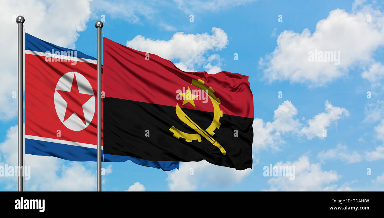 North Korea and Angola flag waving in the wind against white cloudy blue sky together. Diplomacy concept, international relations. - Stock Image