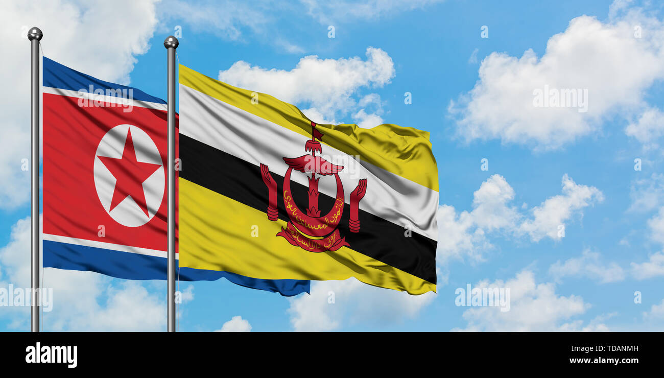 North Korea and Brunei flag waving in the wind against white cloudy blue sky together. Diplomacy concept, international relations. - Stock Image