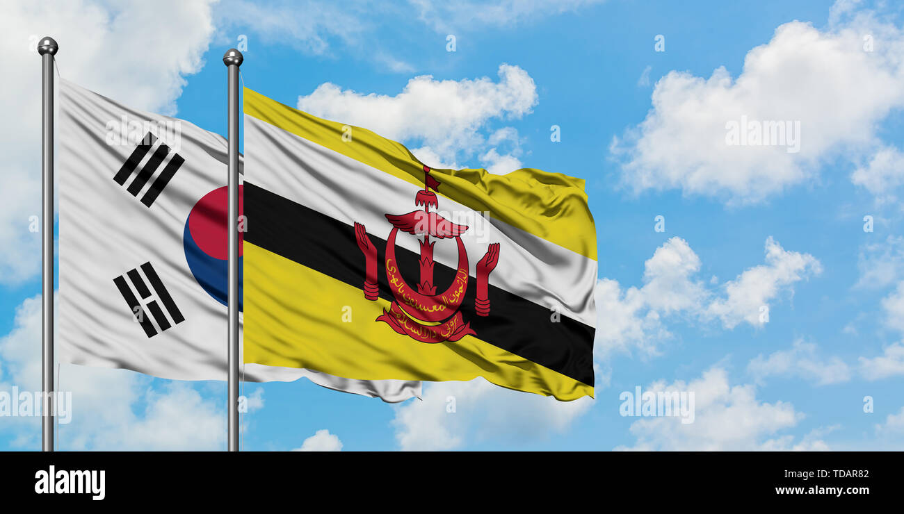South Korea and Brunei flag waving in the wind against white cloudy blue sky together. Diplomacy concept, international relations. - Stock Image
