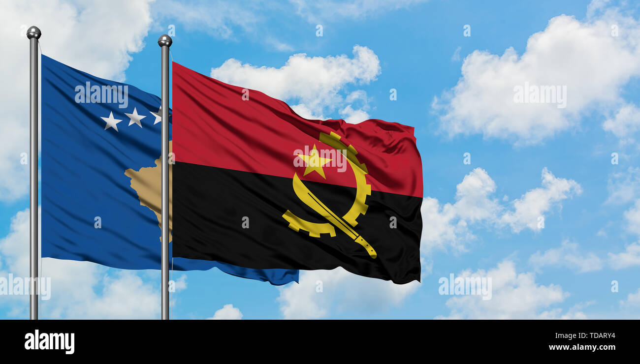 Kosovo and Angola flag waving in the wind against white cloudy blue sky together. Diplomacy concept, international relations. - Stock Image