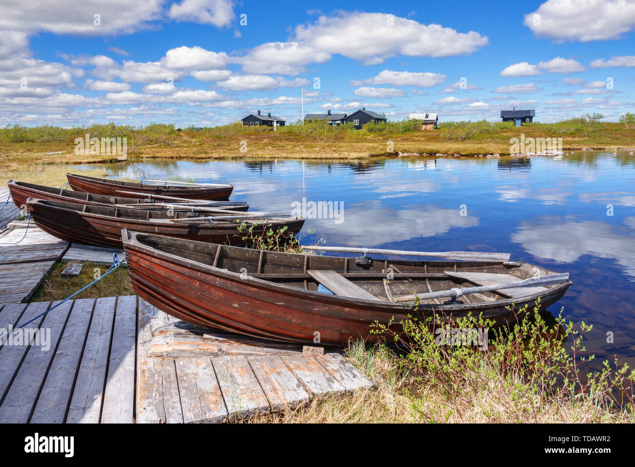 Rowing boats on a jetty by a lake - Stock Image