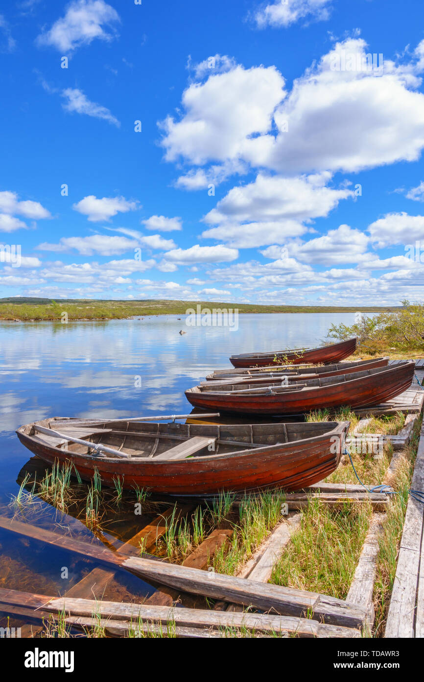 Rowing boats at a jetty in a lake at the highlands in the north - Stock Image