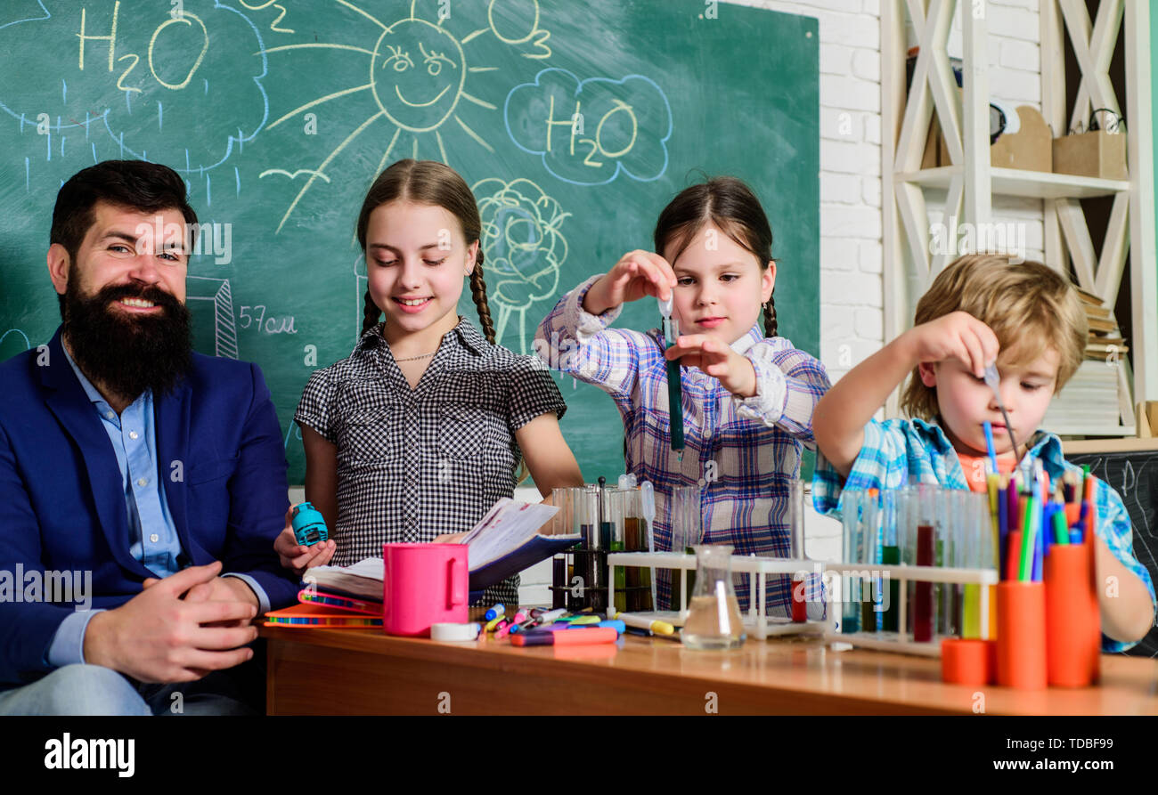 After school clubs. School chemistry experiment. Explaining chemistry to kid. Fascinating chemical reaction. Teacher and pupils test tubes in classroom. Interesting school classes. School education. - Stock Image