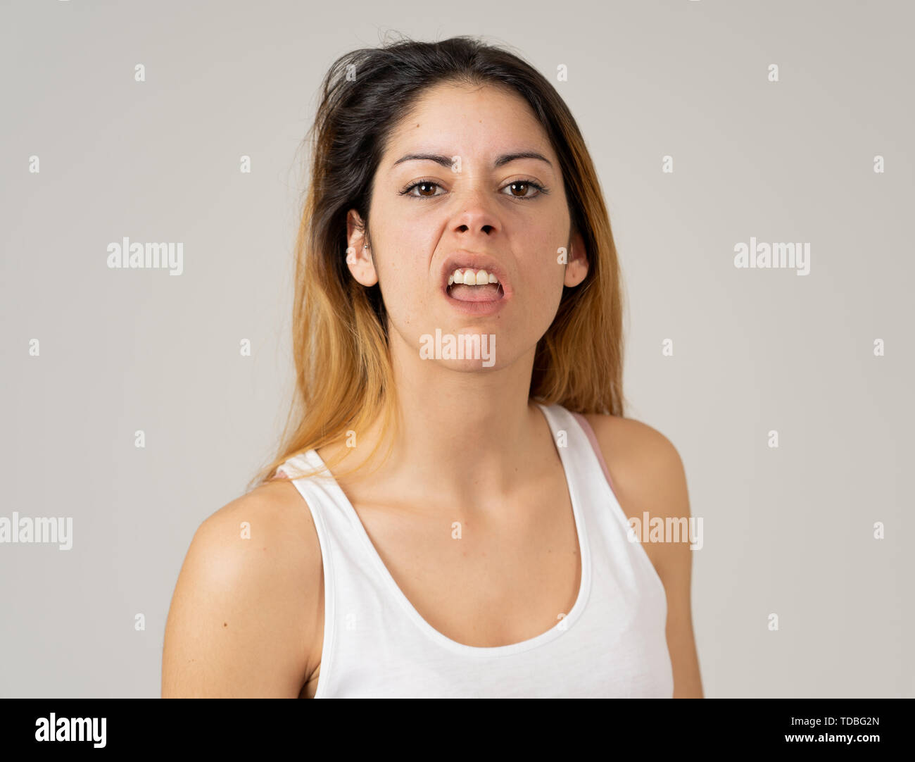 Facial expressions, emotions Anger. Young attractive caucasian woman with angry face. Looking mad and aggressive making furious gestures. Studio portr - Stock Image