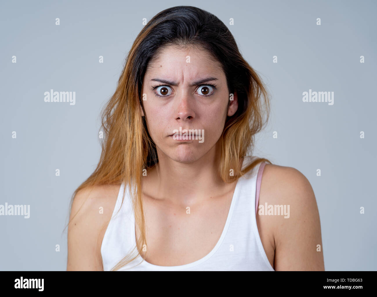 Young woman feeling scared and shocked making fear, anxiety gestures. Looking terrified and desperate. People and Human emotions and Violence and aggr - Stock Image