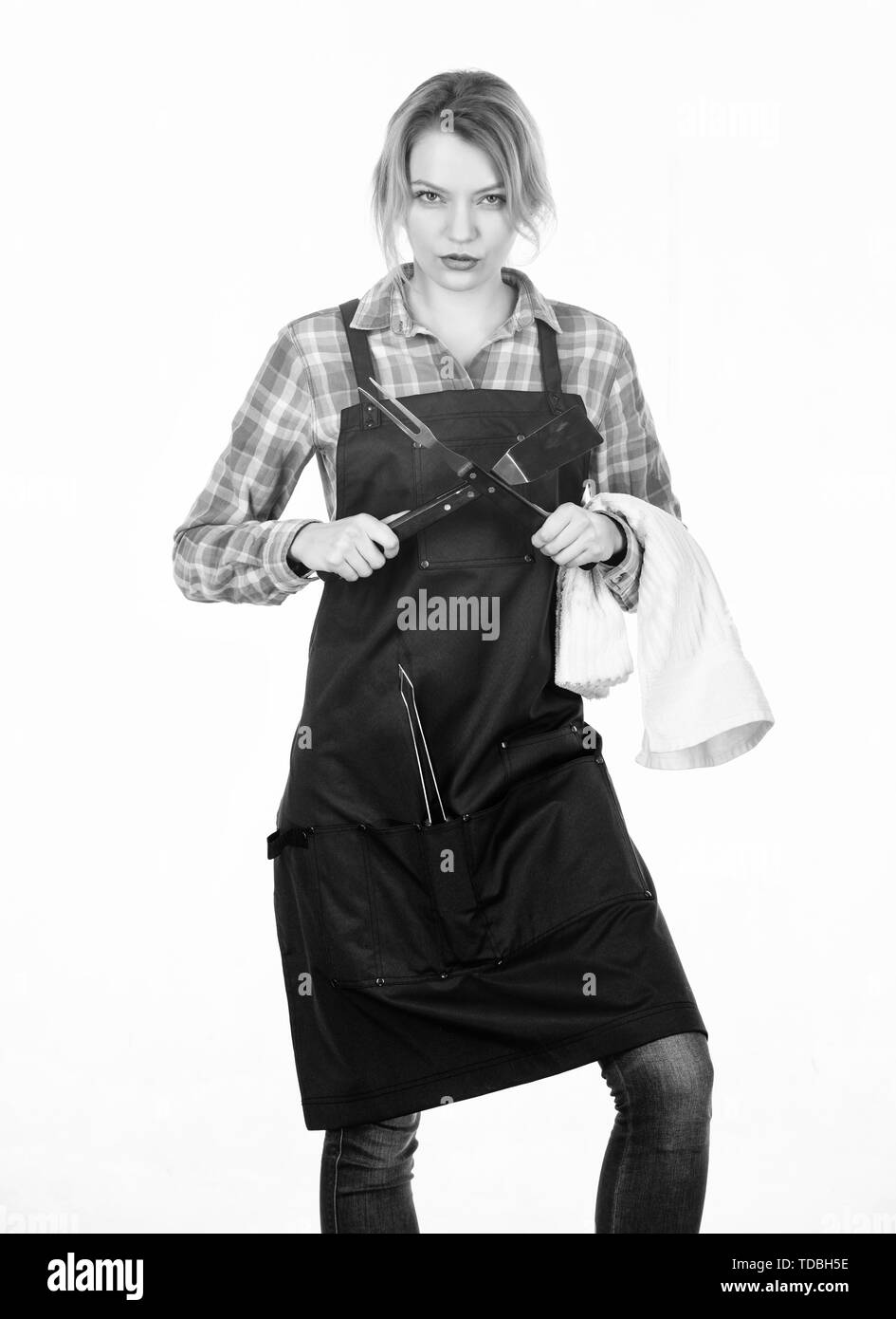 She loves her job. Pretty girl in chef apron. Preparation and culinary. Woman hold kitchen utensils. Tools for roasting meat outdoor. Picnic barbecue. food cooking recipe. Family weekend. - Stock Image