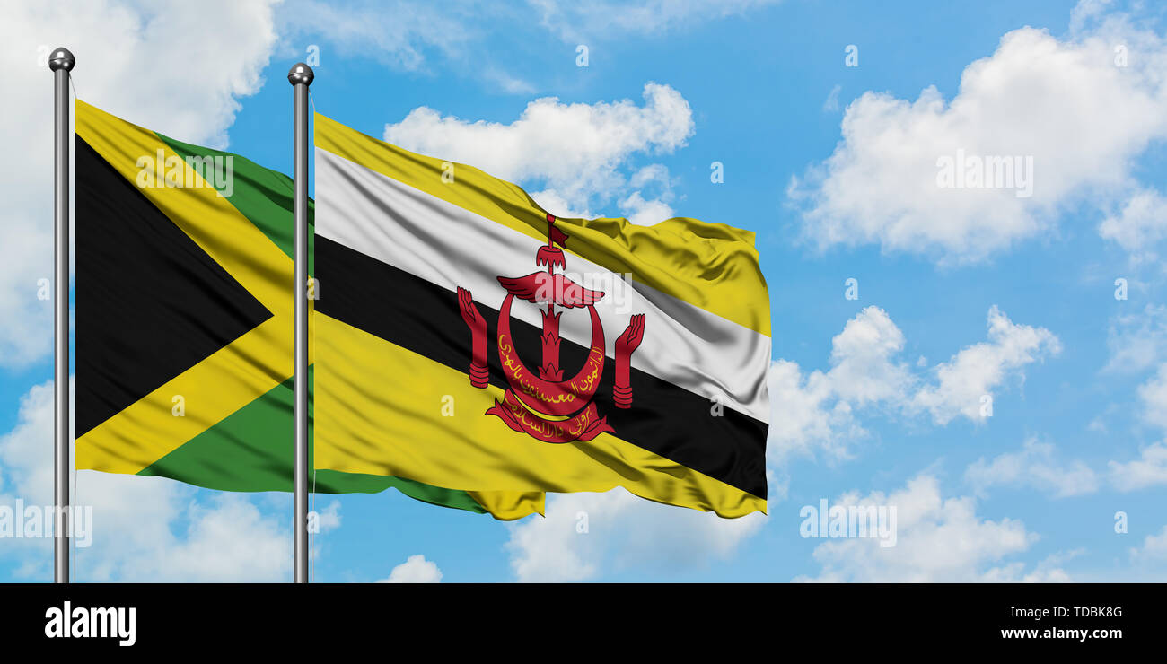 Jamaica and Brunei flag waving in the wind against white cloudy blue sky together. Diplomacy concept, international relations. - Stock Image