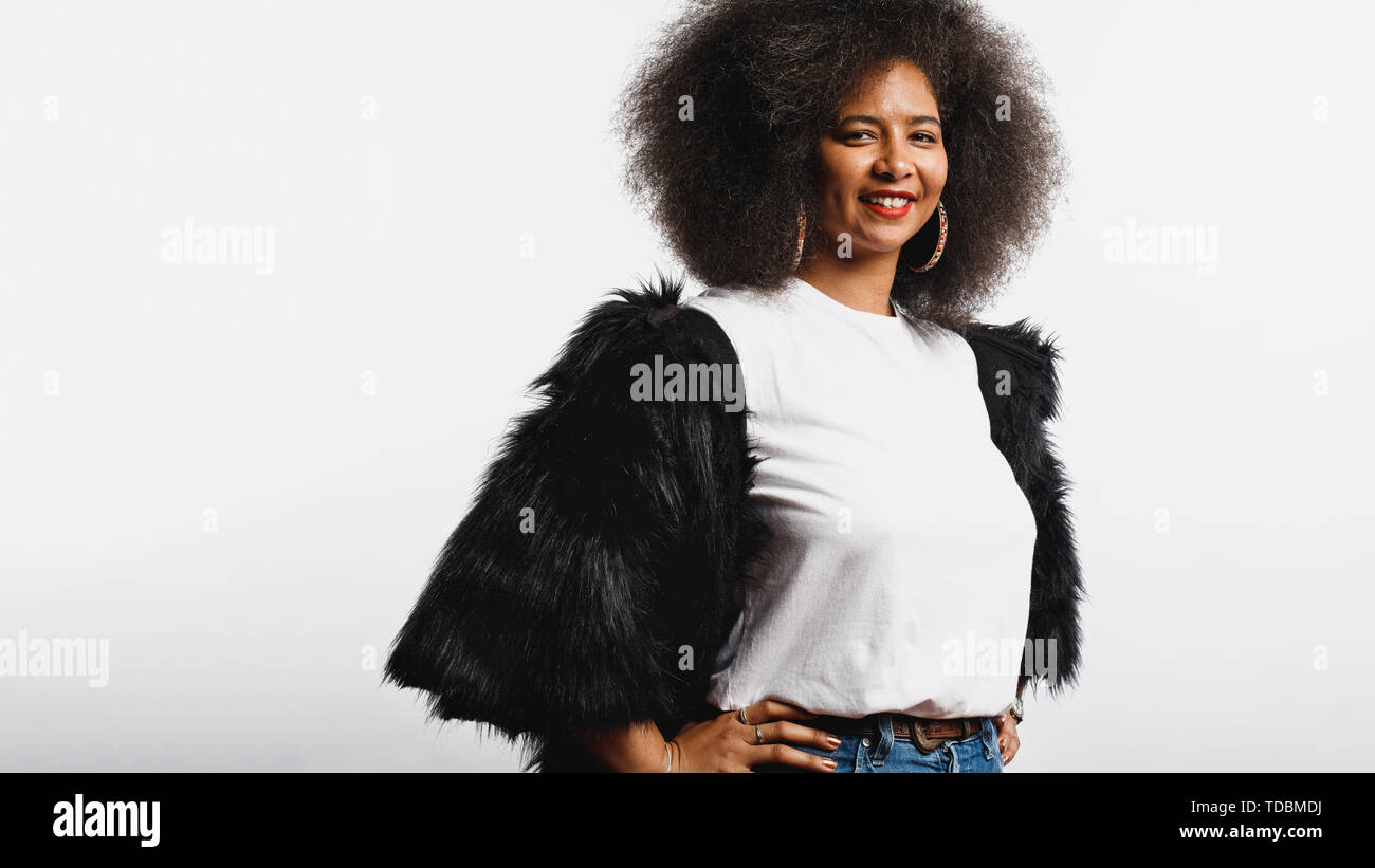 Smiling woman in afro hairstyle standing against white background. Portrait of cheerful woman in fur coat looking at camera. Stock Photo