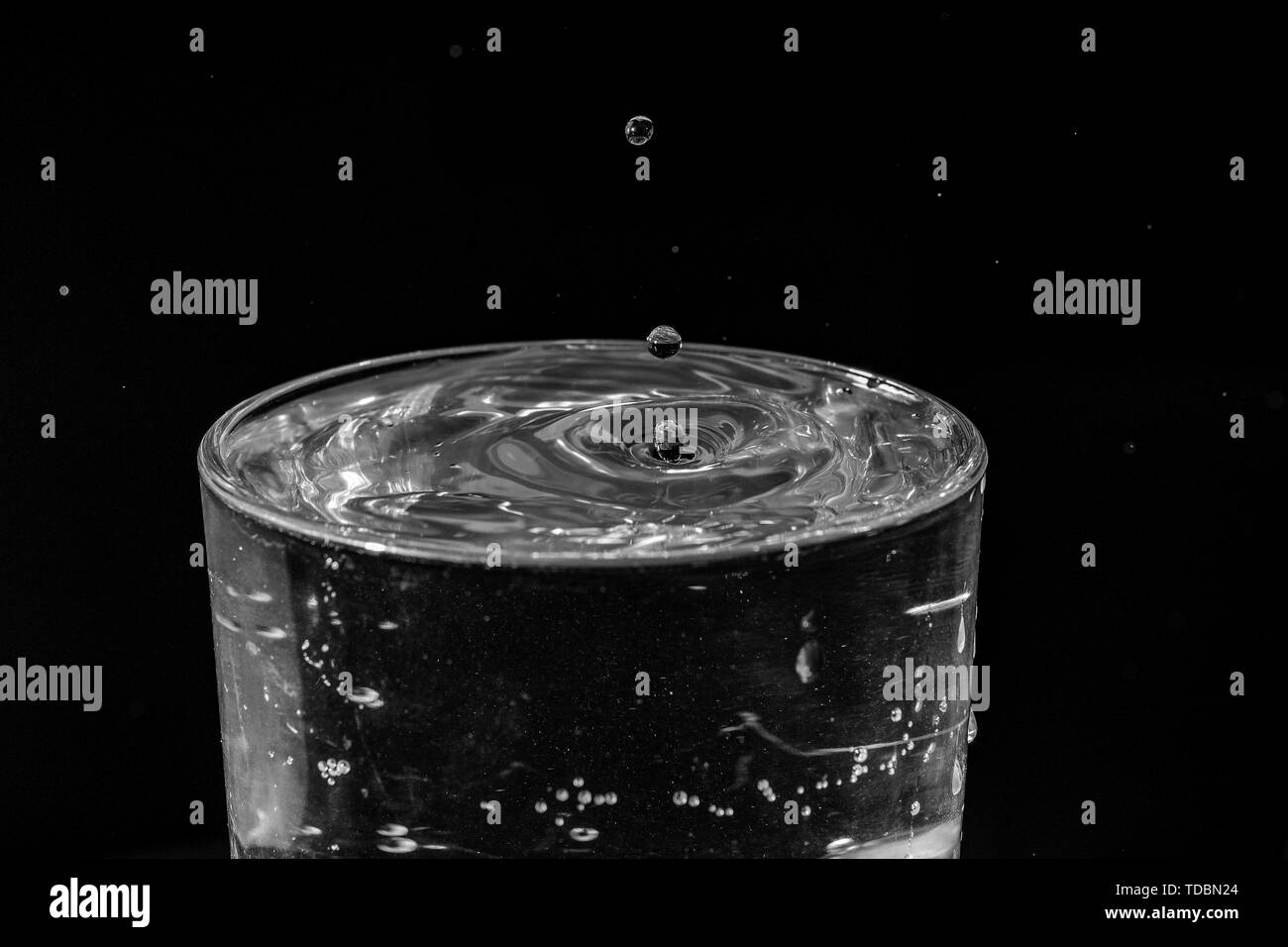 water drops splashing in the glass of water on black background - Stock Image