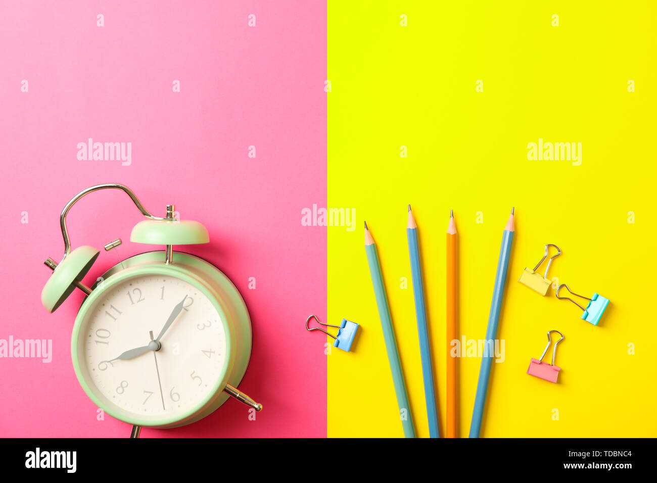 Composition with alarm clock, pencils and clips on two tone background, space for text - Stock Image