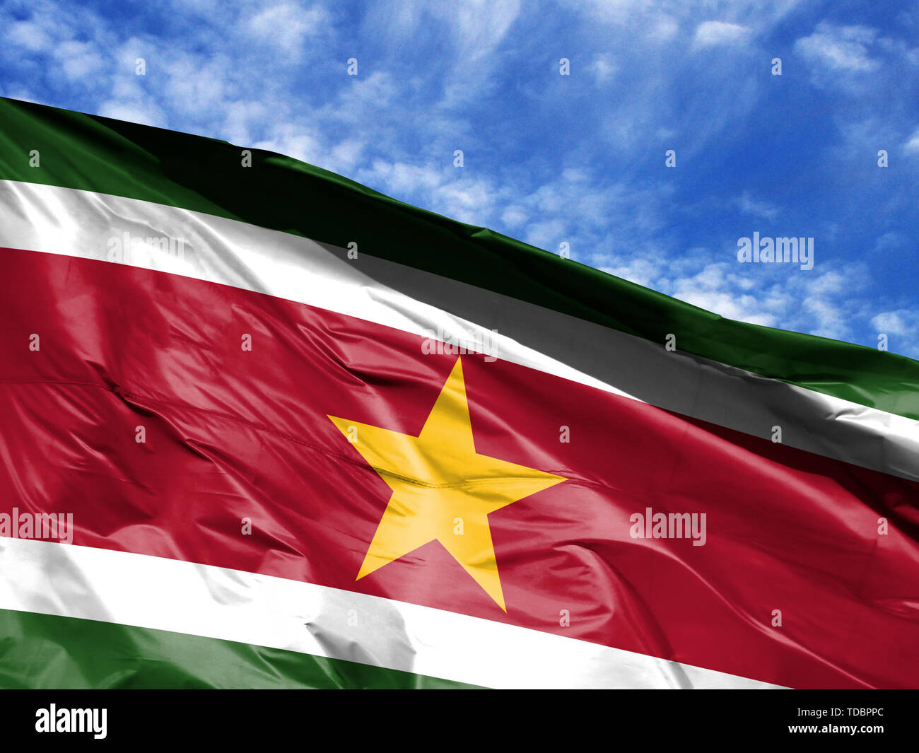 waving flag of Suriname close up against blue sky - Stock Image