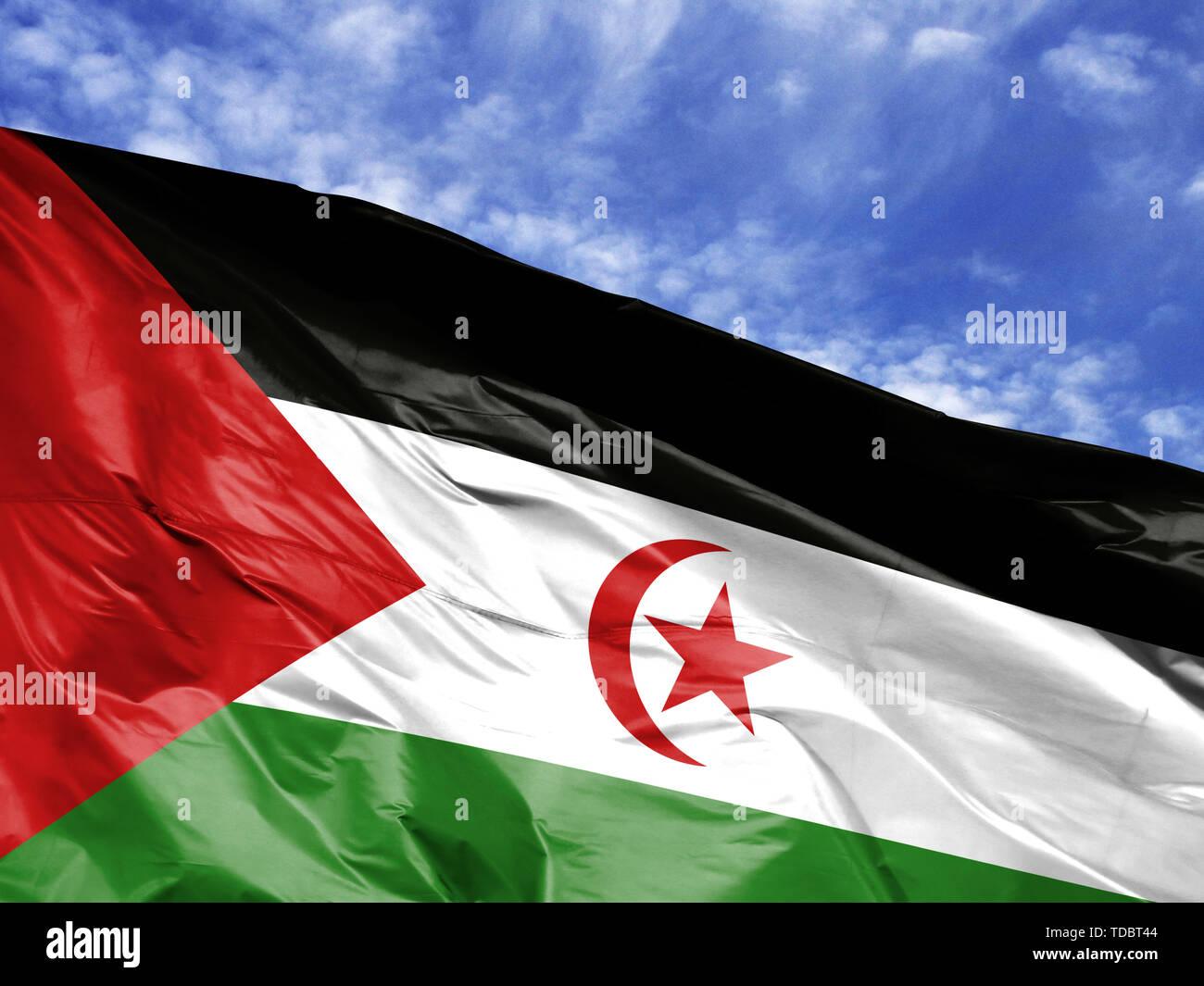 waving flag of Western Sahara close up against blue sky - Stock Image