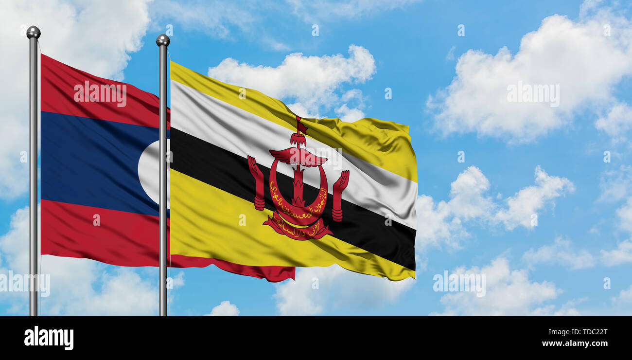 Laos and Brunei flag waving in the wind against white cloudy blue sky together. Diplomacy concept, international relations. - Stock Image