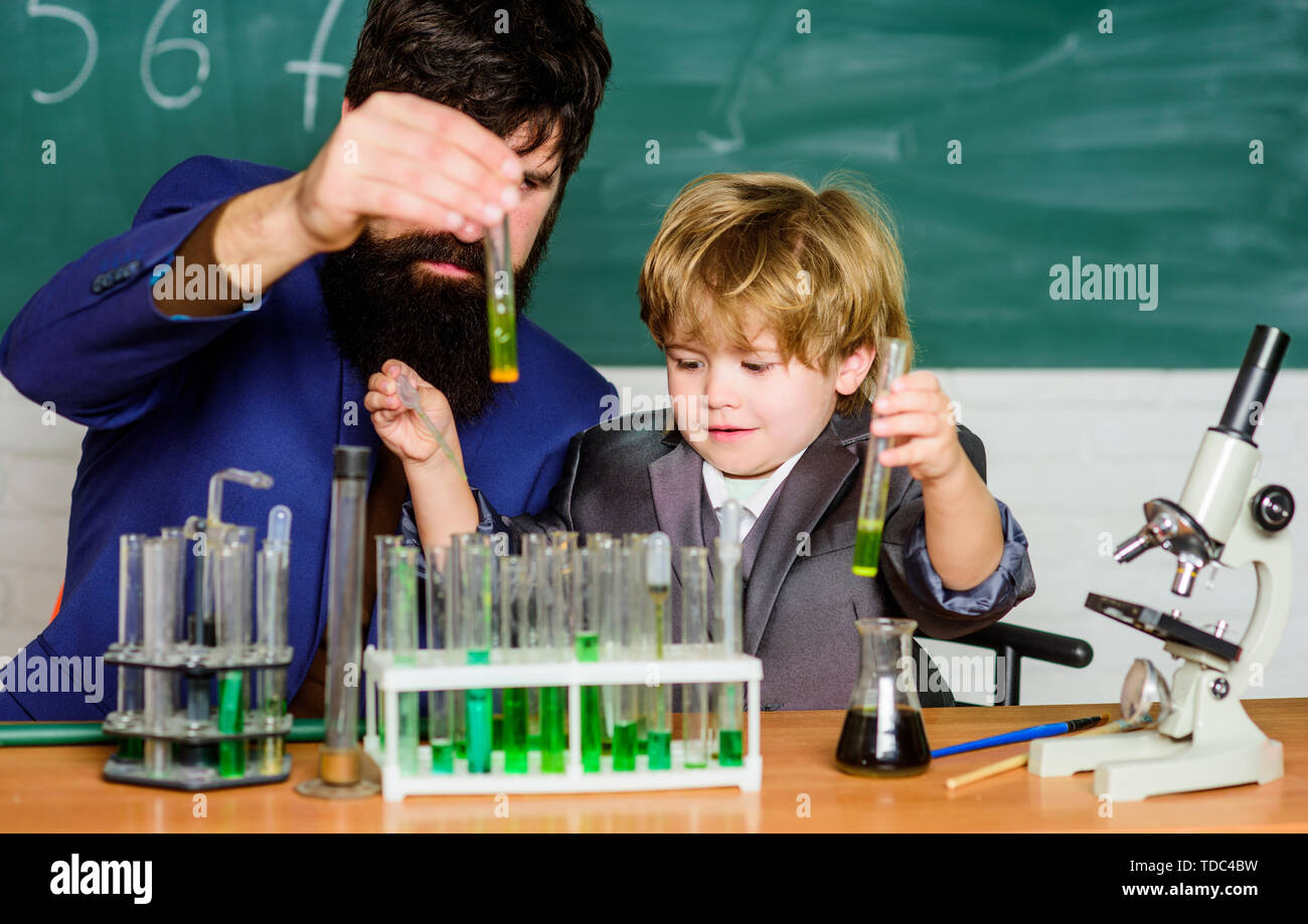 Back to school. Explaining biology to child. father and son at school. biotechnoloy research concept. Chemistry and physics biology. bearded man teacher with little boy. Act the way you want to feel. Stock Photo