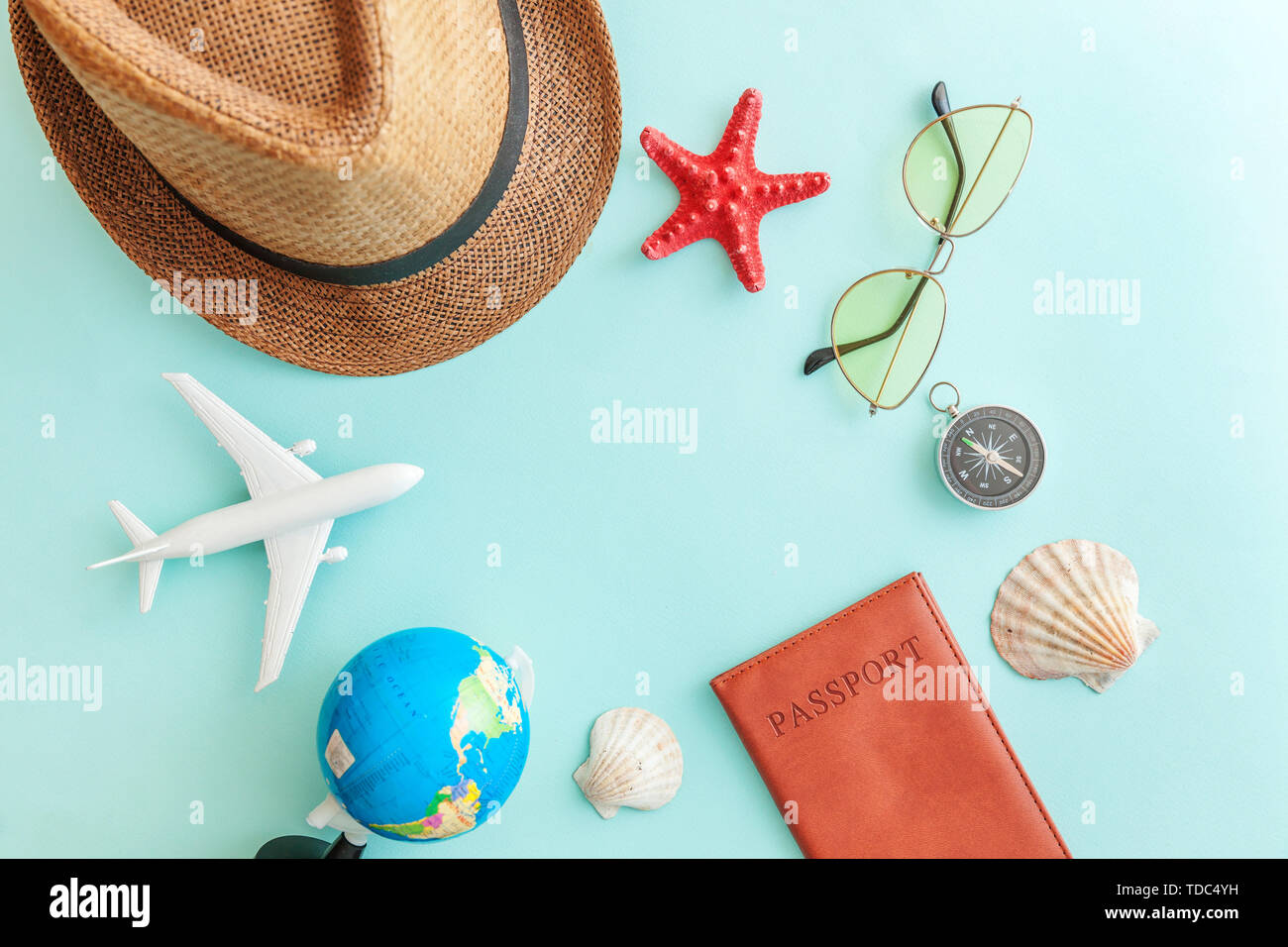 Vacation travel adventure trip concept. Minimal simple flat lay with plane passport sunglasses globe hat compass and shell on blue pastel colourful tr - Stock Image