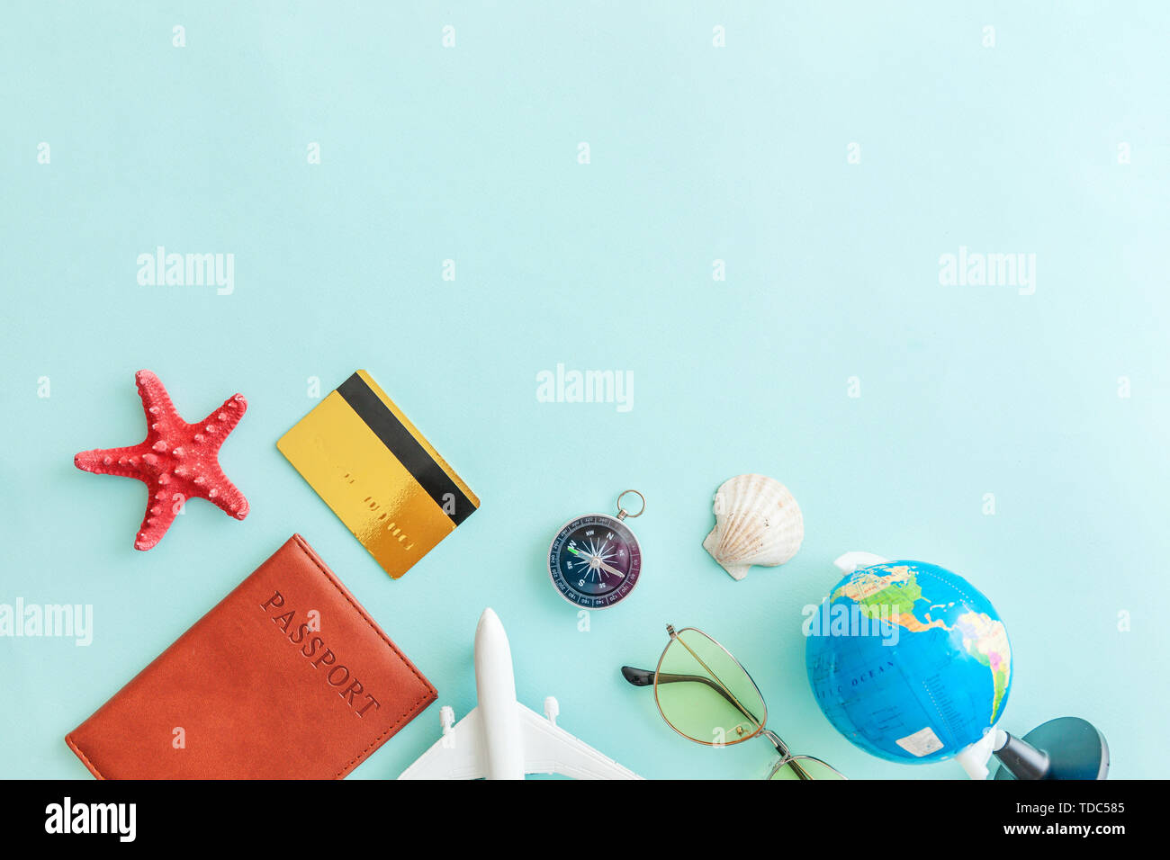 Vacation travel adventure trip concept. Minimal simple flat lay with plane passport sunglasses globe gold credit card and shell on blue pastel colourf - Stock Image