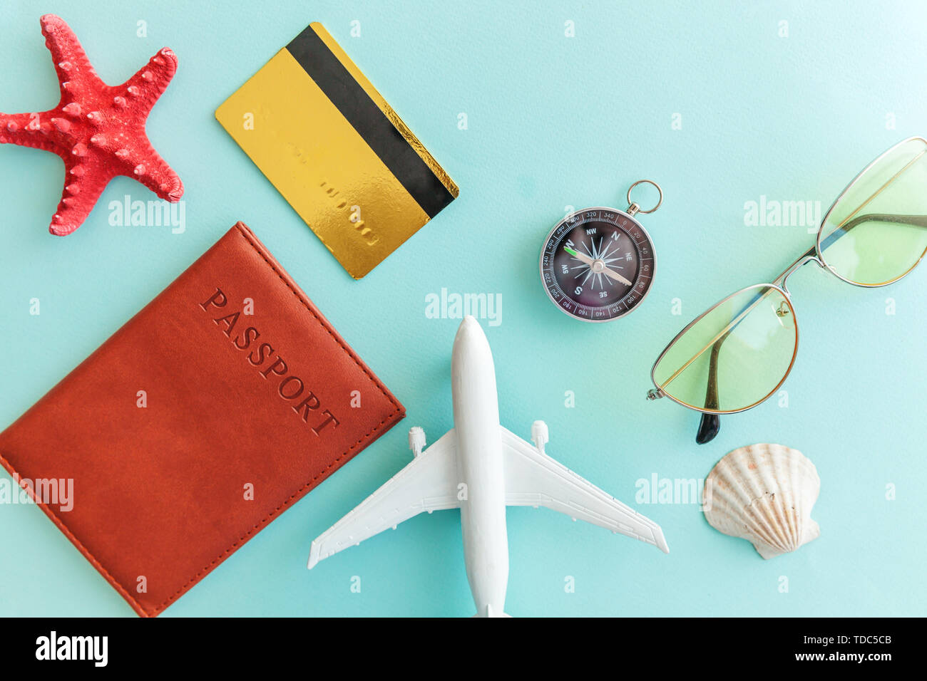 Vacation travel adventure trip concept. Minimal simple flat lay with plane passport sunglasses compass gold credit card shell on blue pastel colourful - Stock Image