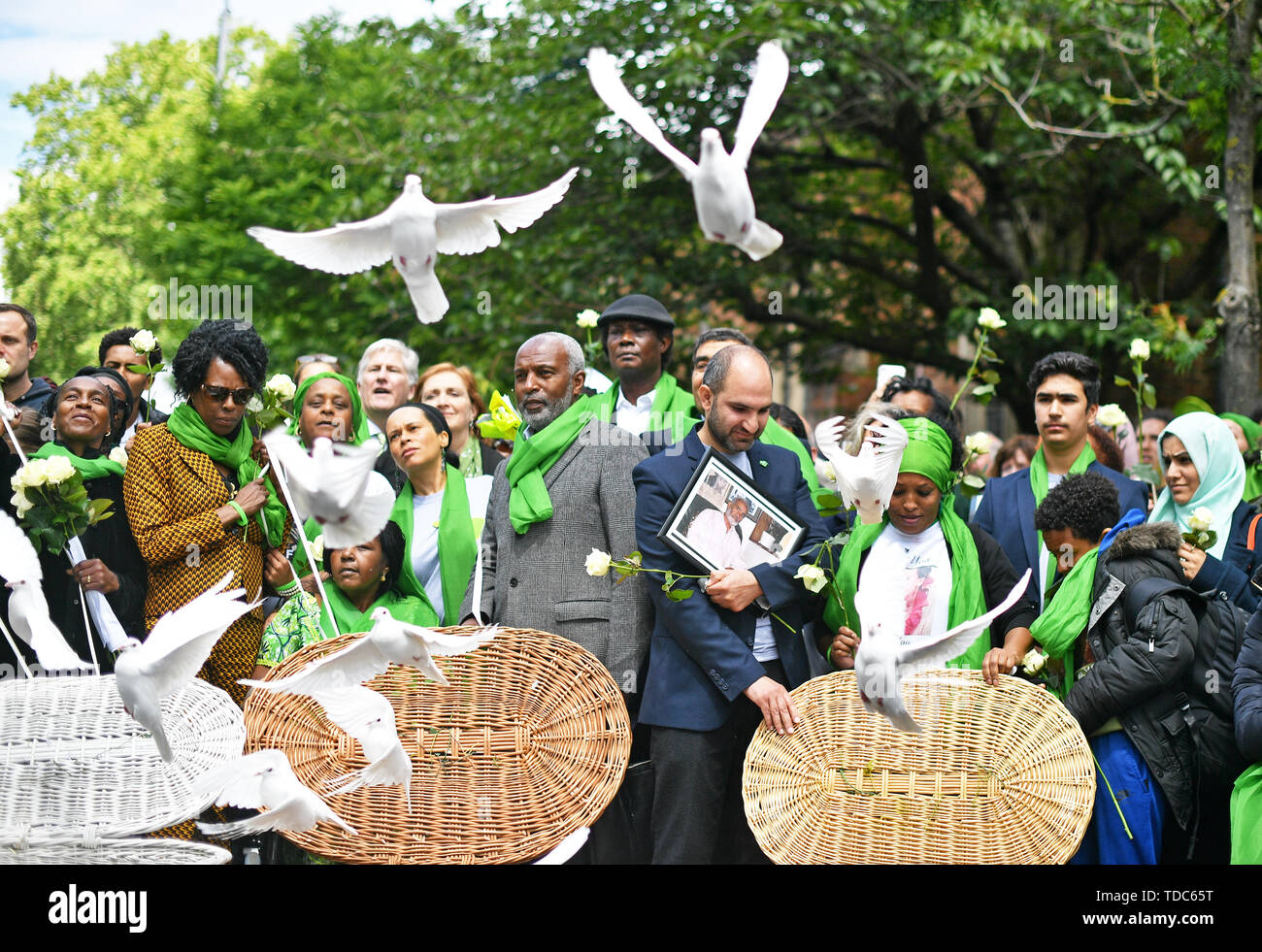 People gather as doves are released outside St Helens church, London, following a service to mark the two-year anniversary of the Grenfell Tower block fire. - Stock Image