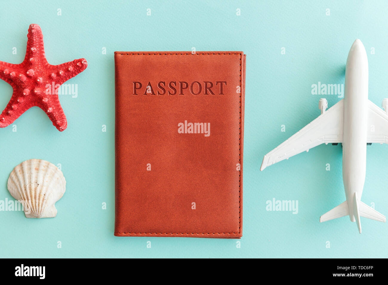 Vacation travel adventure trip concept. Minimal simple flat lay with plane passport and shell on blue pastel colourful trendy background. Tourist esse - Stock Image