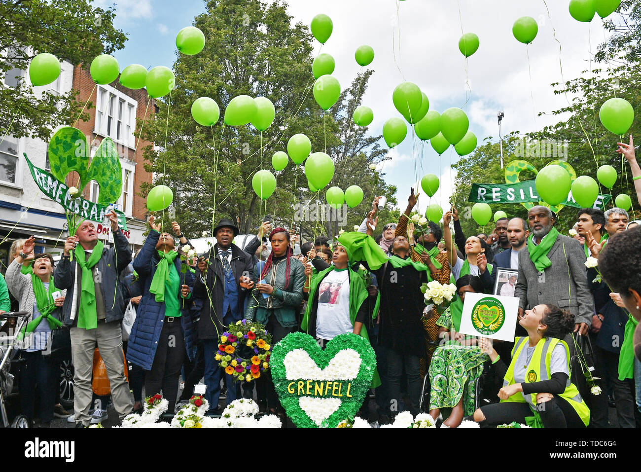 People gather as balloons are released outside St Helens church, London, following a service to mark the two-year anniversary of the Grenfell Tower block fire. - Stock Image