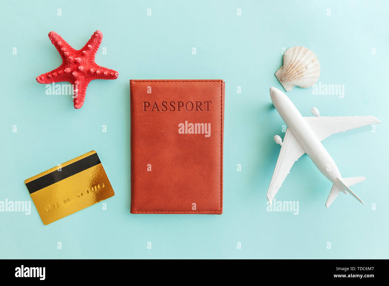 Vacation travel adventure trip concept. Minimal simple flat lay with plane passport gold credit card and shell on blue pastel colourful trendy backgro - Stock Image