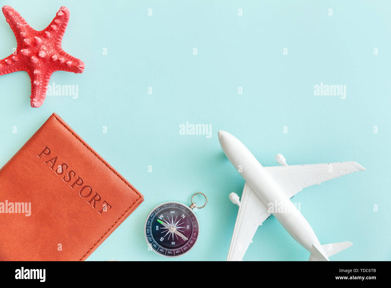 Vacation travel adventure trip concept. Minimal simple flat lay with plane passport compass and shell on blue pastel colourful trendy background. Tour - Stock Image