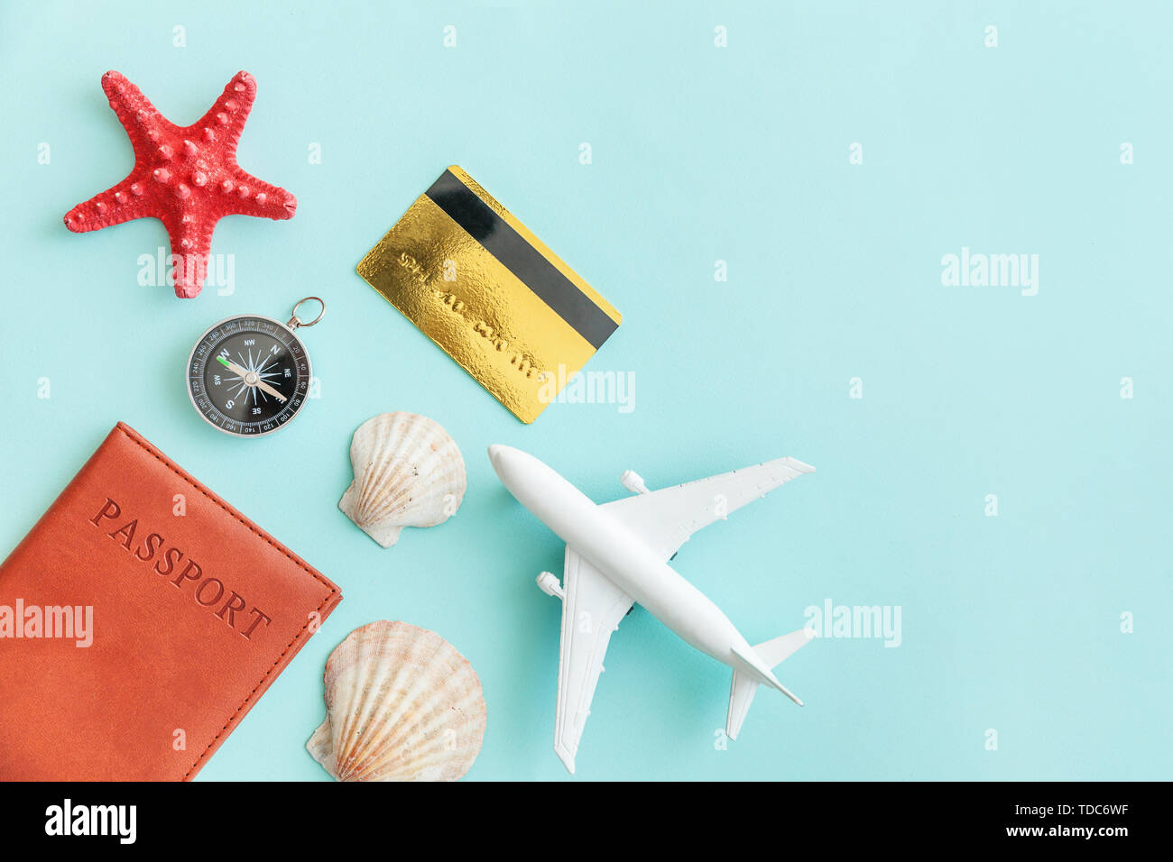 Vacation travel adventure trip concept. Minimal simple flat lay with plane passport compass gold credit card and shell on blue pastel colourful trendy - Stock Image