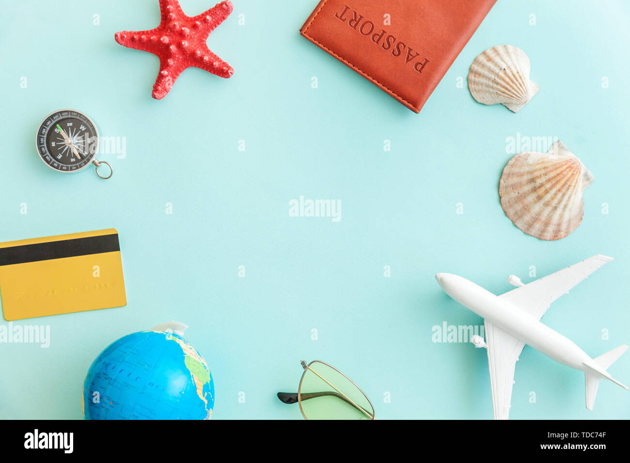 Vacation travel adventure trip concept. Minimal simple flat lay with plane passport sunglasses globe gold credit card and shell on blue pastel colourful trendy background Tourist essentials Copy space - Stock Image