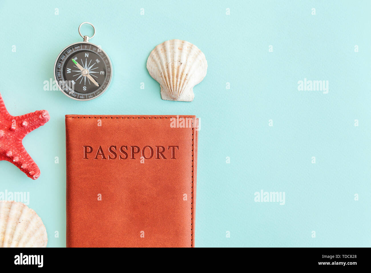 Vacation travel adventure trip concept. Minimal simple flat lay with passport compass and shell on blue pastel colourful trendy background. Tourist essentials Copy space - Stock Image