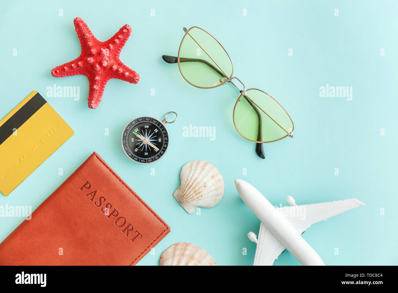 Vacation travel adventure trip concept. Minimal simple flat lay with plane passport sunglasses compass gold credit card shell on blue pastel colourful trendy background. Tourist essentials - Stock Image