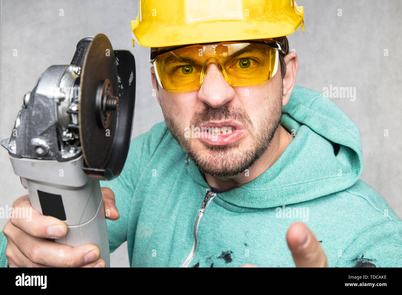 the construction worker holds an angle grinder in his hand - Stock Image
