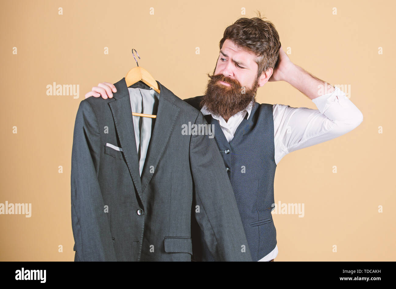 Thinking of what to wear to formal event. Hipster choosing formal suit jacket in wardrobe. Bearded man at formal wear boutique. Classy formal look of fashion model. - Stock Image