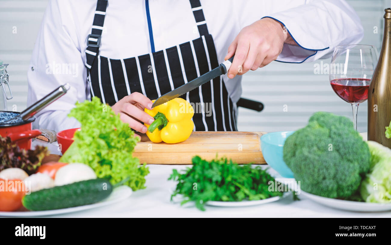 Useful for significant amount of cooking methods. Basic cooking processes. Man master chef or amateur cooking food. Sharp knife chopping vegetable. According to recipe. Prepare ingredient for cooking. - Stock Image