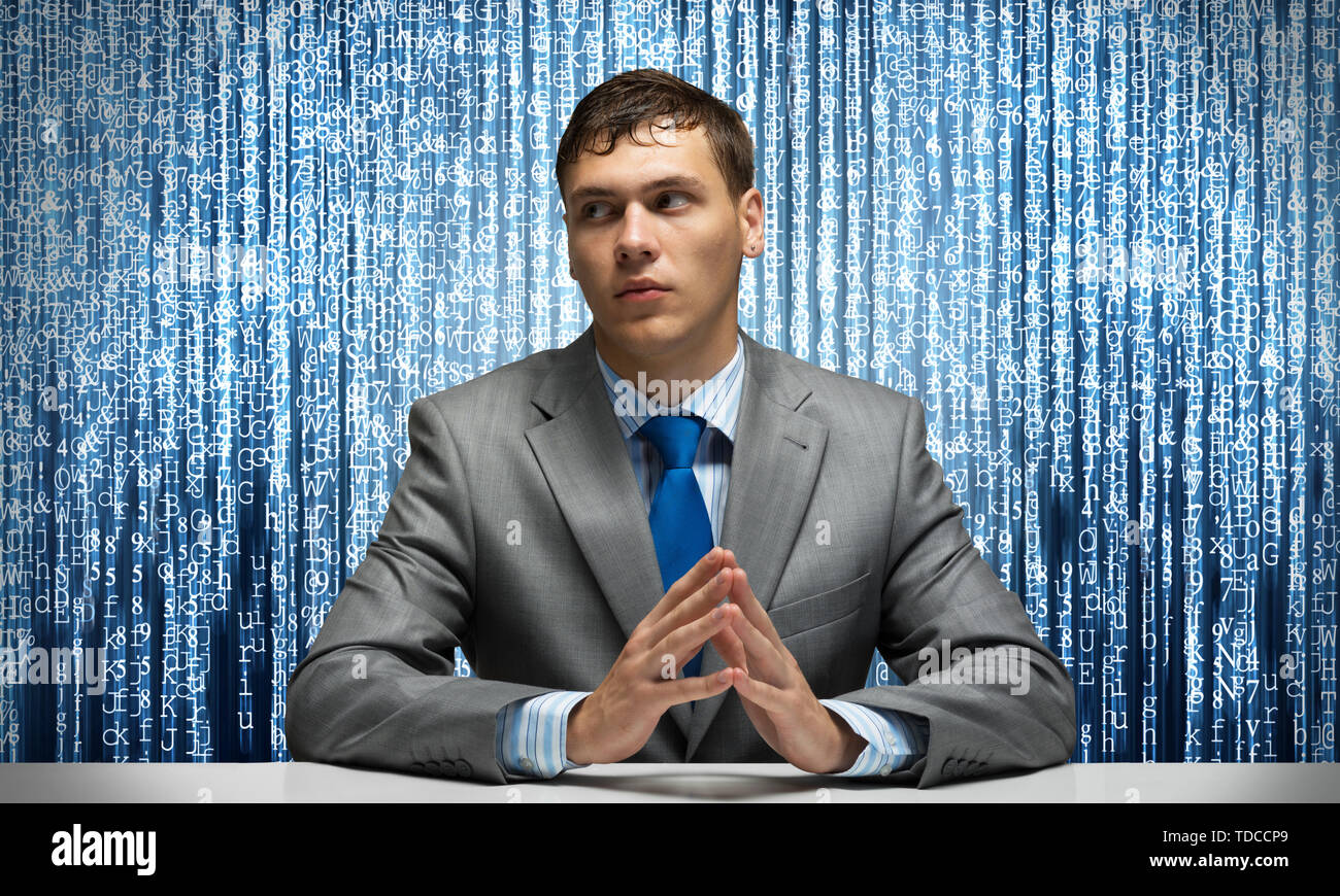 Young serious man folded hands and sitting at desk. Digital technologies and online data stream. Portrait of businessman wears business suit and tie o - Stock Image