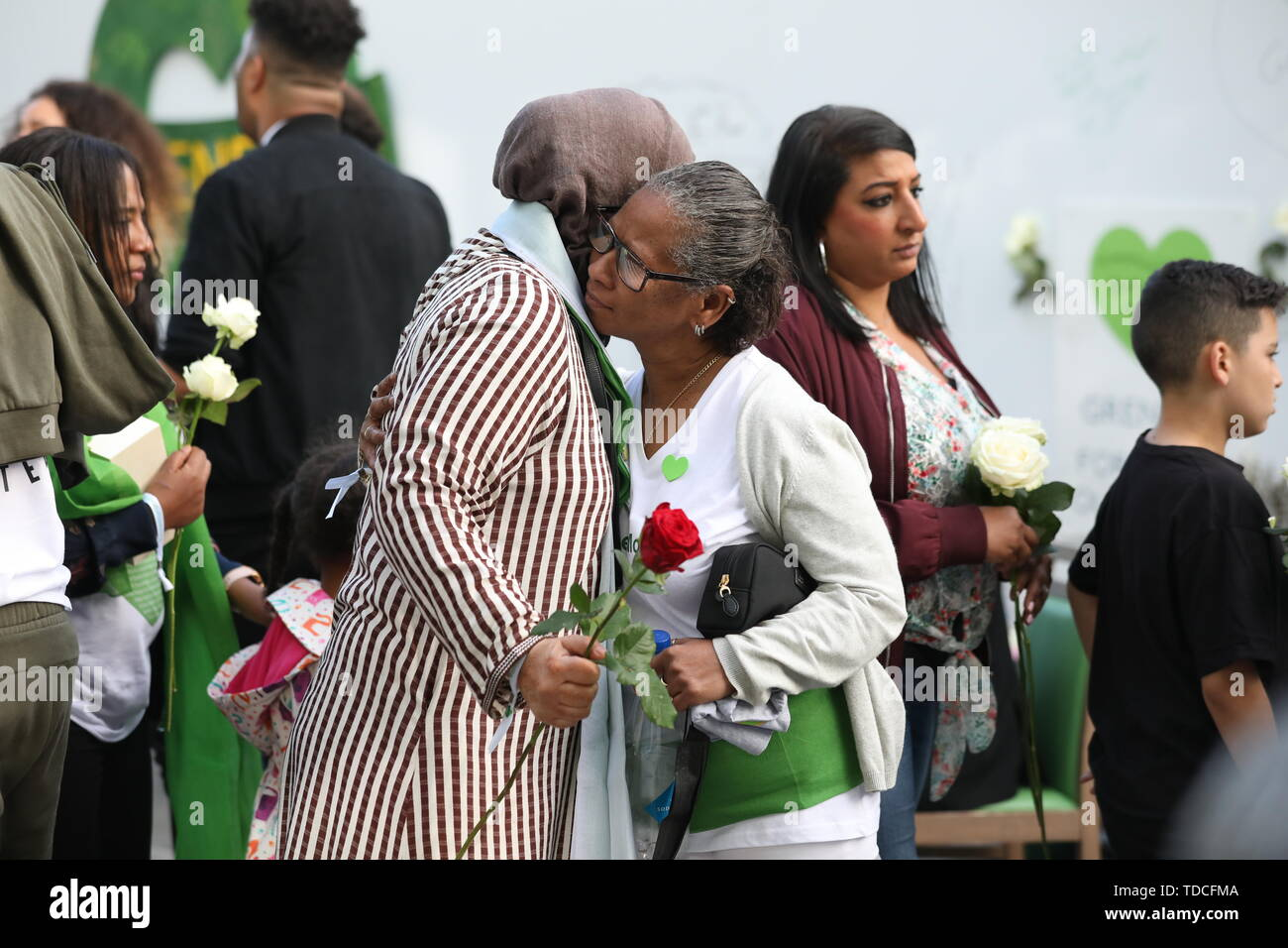 Family and friends of the 72 people who lost their lives in the Grenfell Tower block during a wreath laying ceremony outside Grenfell Tower, London, to mark the two-year anniversary. - Stock Image