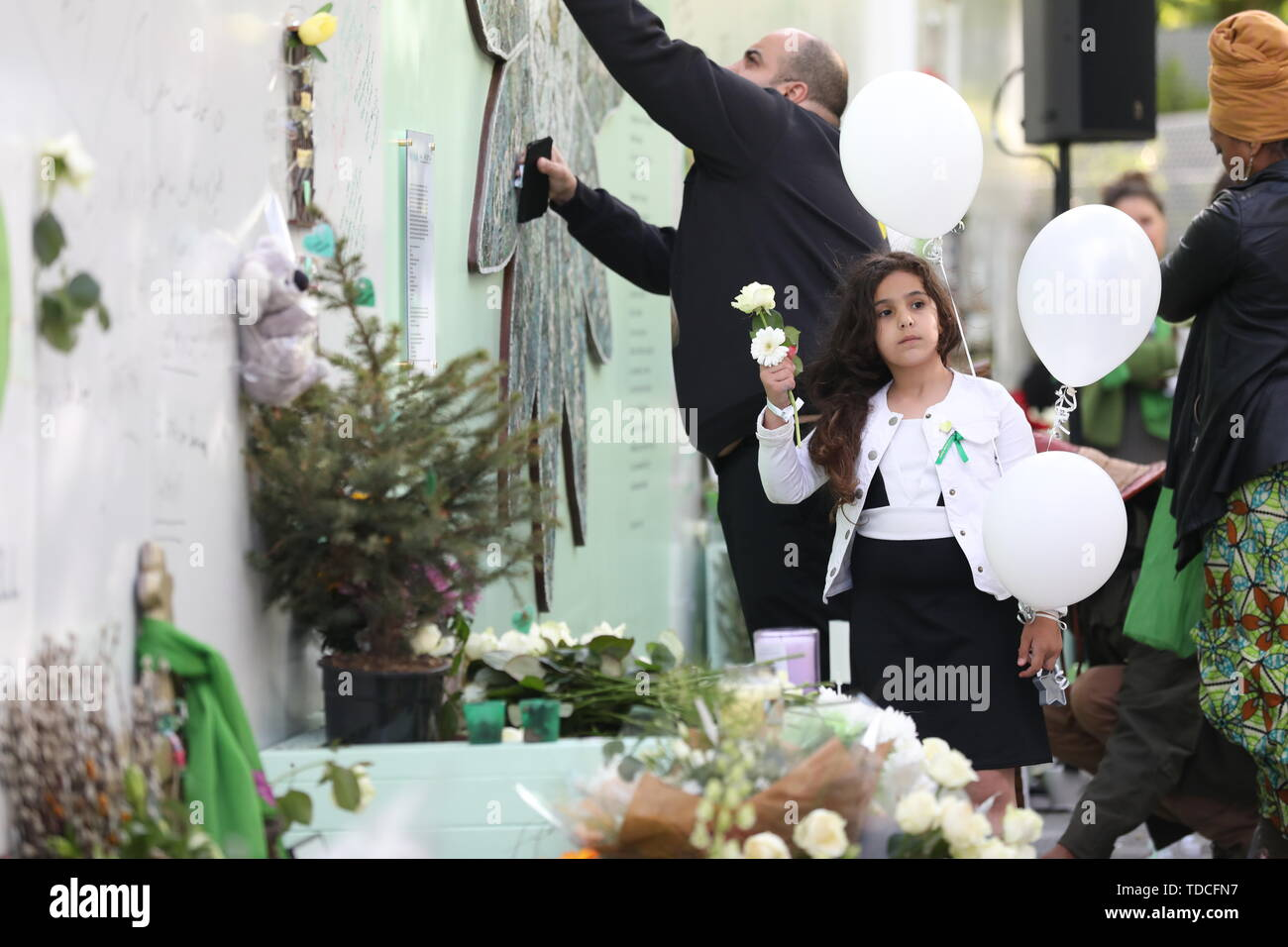 Family and friends of the 72 people who lost their lives in the Grenfell Tower block lay flowers and write messages during a wreath laying ceremony outside Grenfell Tower, London, to mark the two-year anniversary. - Stock Image
